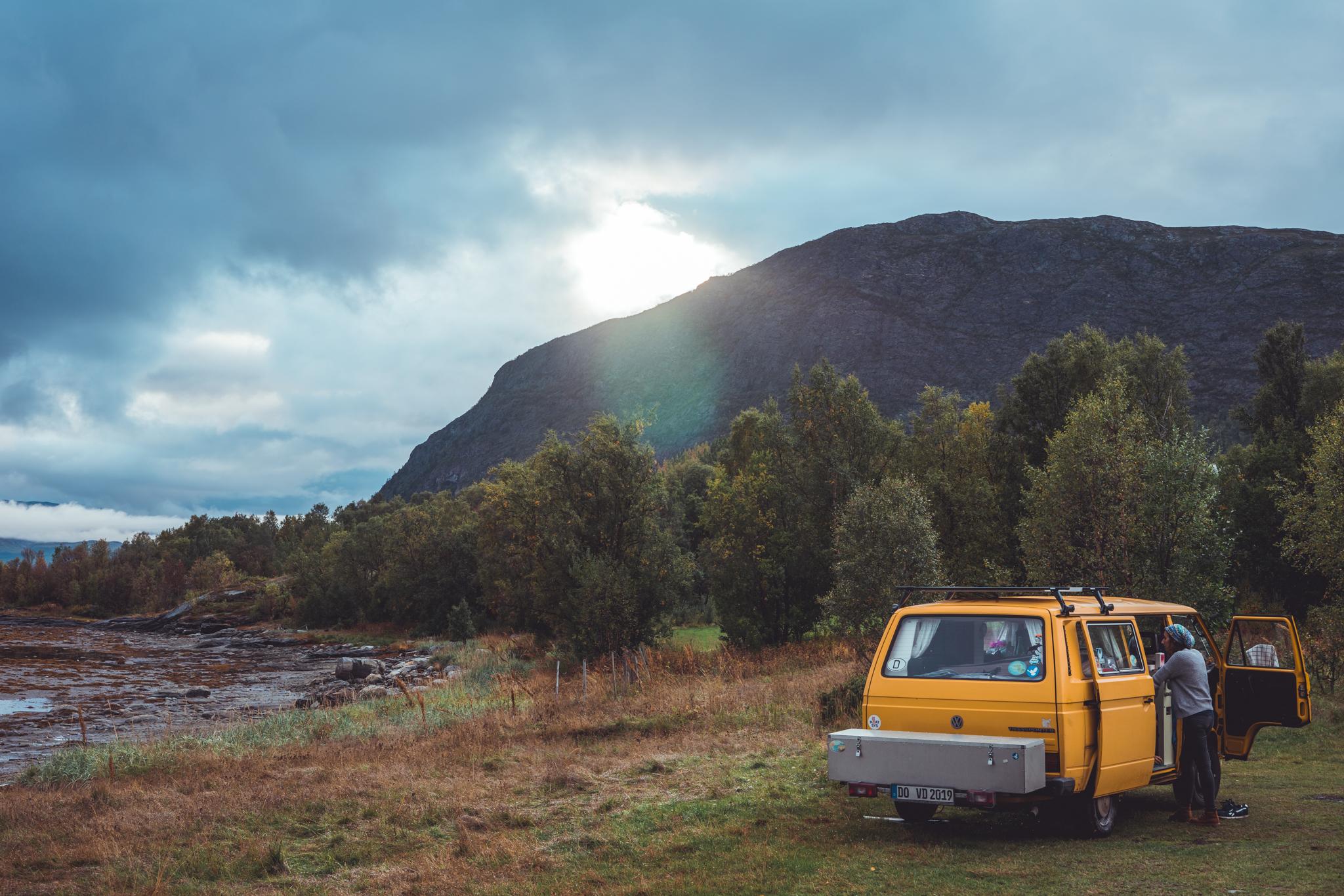 Foto als sfeerbeeld van een camperbusje in de bergen met ondergaande zon